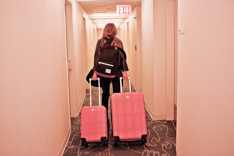 Frank Body' babe wheeling her pink suitcase through hotel. She is about to use her travel skincare kit, The Grind high club. The mini travel satchel contains four coffee scrubs in four scents.