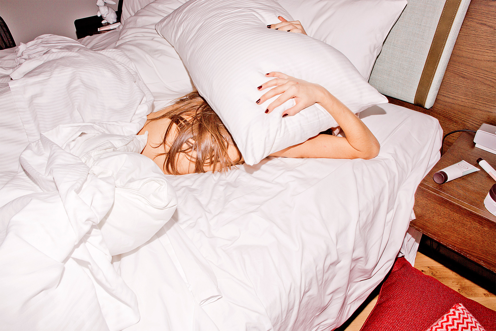 girl laying in bed with pillow over head